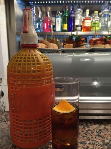 No vermut pode se colocar um pedaço de laranja ou de limão. Esta garrafa é onde está a soda para adicionar ao vermut.